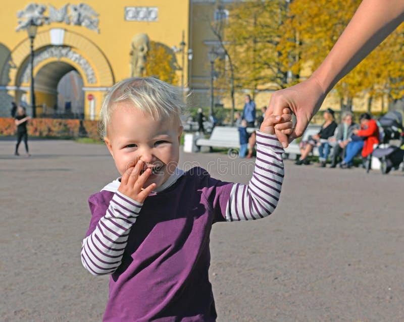 L'enfant heureux tient la main de la mère sur la promenade image libre de droits