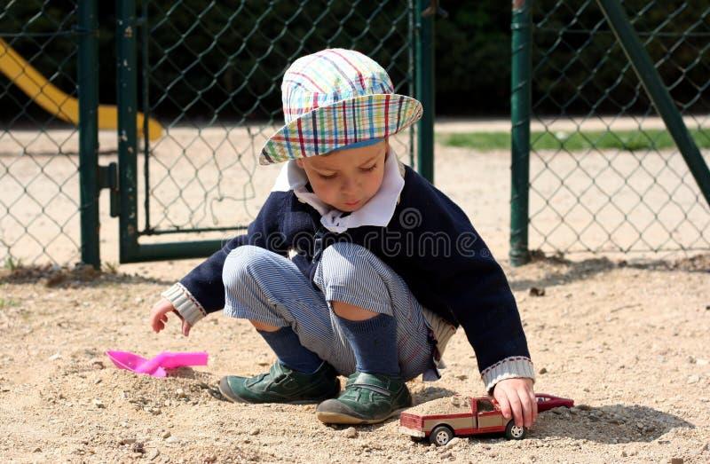 L'enfant joue avec des jouets sur une cour de jeu images libres de droits