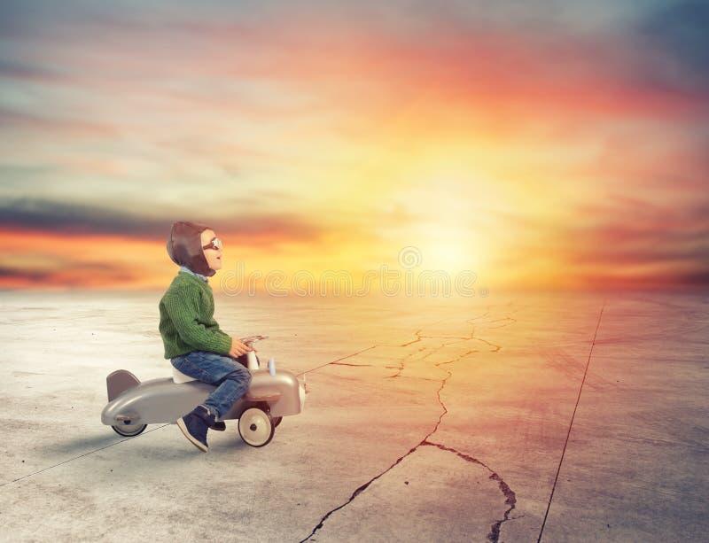 L'enfant joue avec un petit avion pendant le coucher du soleil photographie stock