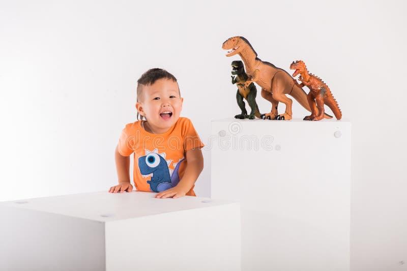 L'enfant joyeux dit quelque chose et sourit à côté de trois jouets de dinosaure photo libre de droits