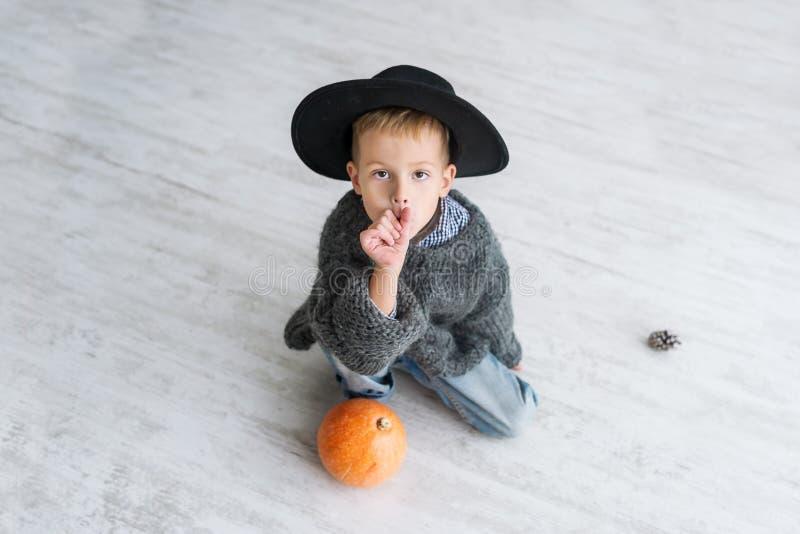 L'enfant juif dans le chapeau noir avec le potiron s'asseyent sur le plancher à l'intérieur image stock