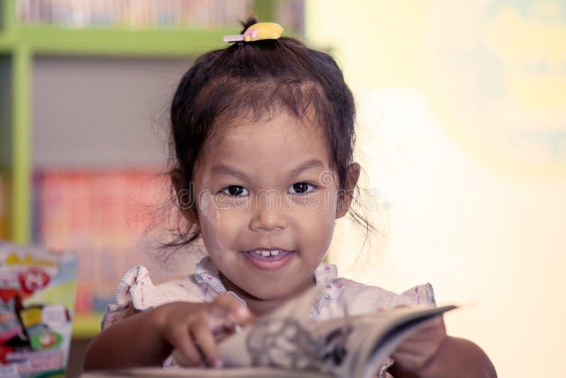 L'enfant a lu, petite fille mignonne lisant un livre photo stock