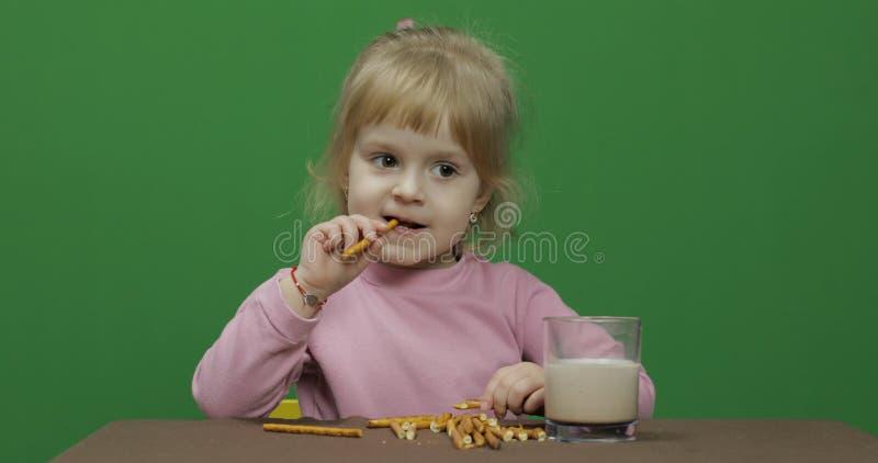 L'enfant mange des biscuits Une petite fille mange des biscuits se reposant sur la table photo stock