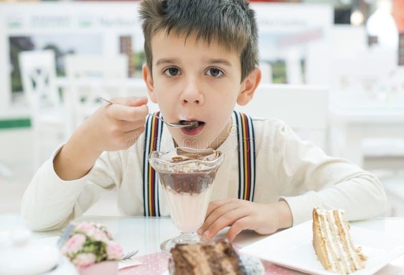 L'enfant mangent la secousse de choco de lait photos stock