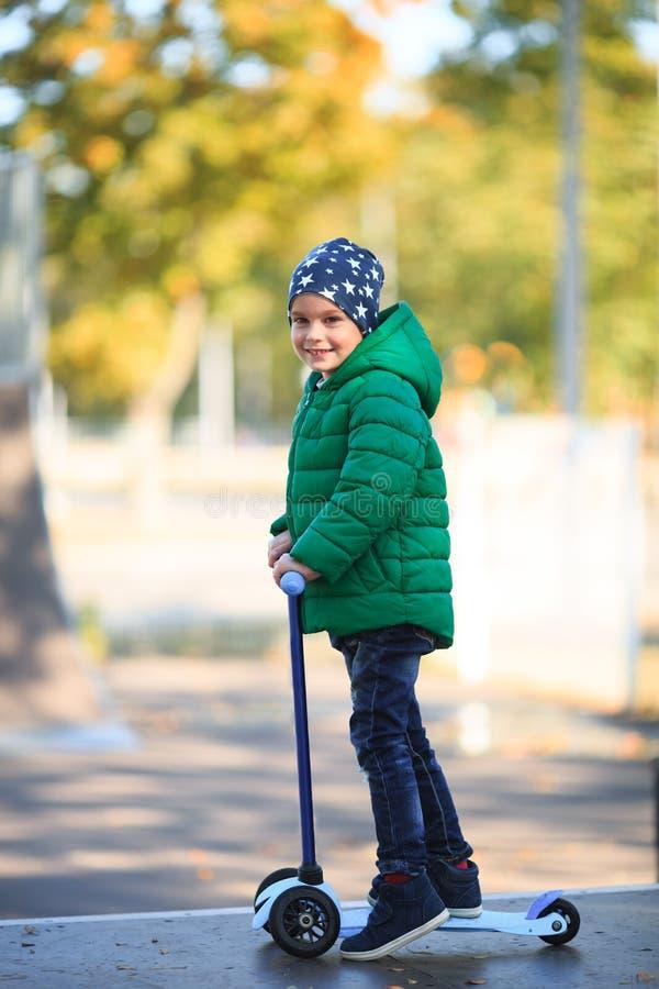 L'enfant marche sur la rue avec un scooter image stock