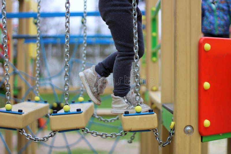 l'enfant marche sur un children& suspendu x27 ; route à chaînes de s sur le terrain de jeu photos libres de droits