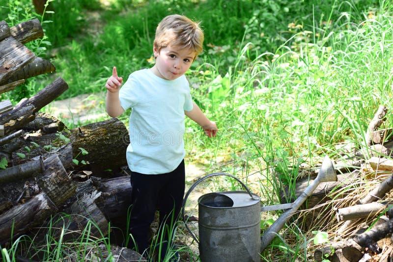 L'enfant mignon a l'idée au sujet de quelque chose Le grand pot d'arrosage est devant peu de garçon entouré par l'herbe L'enfant  image libre de droits