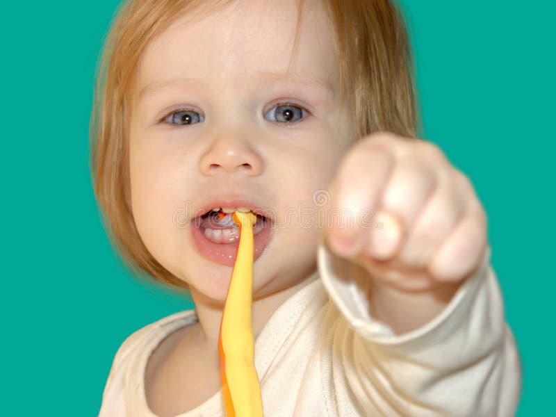 L'enfant montre le poing avec le pouce entre le milieu et l'index image libre de droits