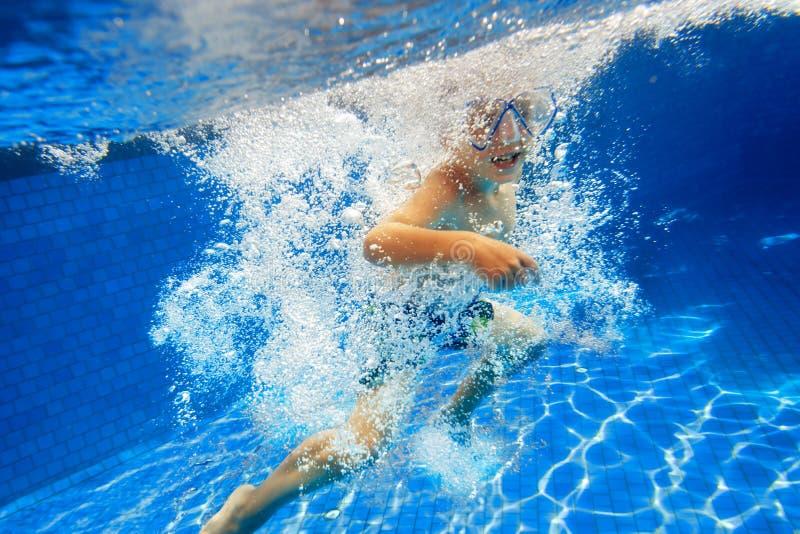 L'enfant nage dans la piscine sous l'eau image stock