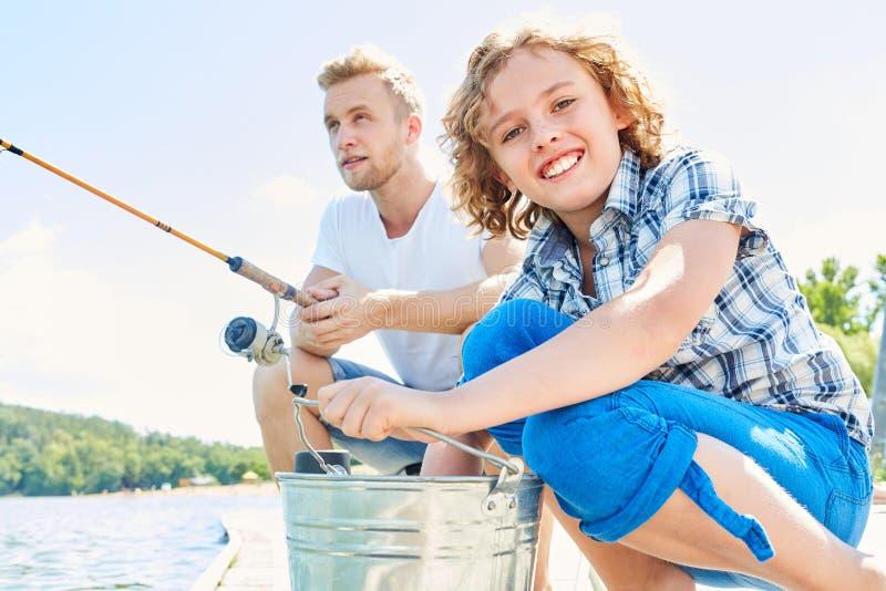 L'enfant pêche ainsi que son père photographie stock libre de droits