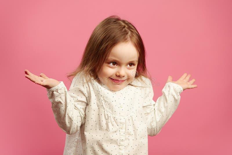 L'enfant perplexe gesticule ses épaules et soulève des mains, exprime l'ignorance ou la difficulté, ne connaît pas la réponse au images stock