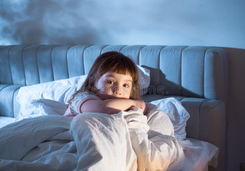L'enfant a peur de se situer dans le lit la nuit images stock