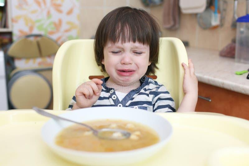 L'enfant pleurant ne veulent pas manger de la soupe photo libre de droits