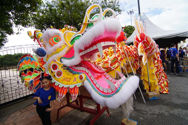 L'enfant prennent la photo devant la plus longue danse de dragon de Penang à l'esplanade Padang Kota Lama photos stock