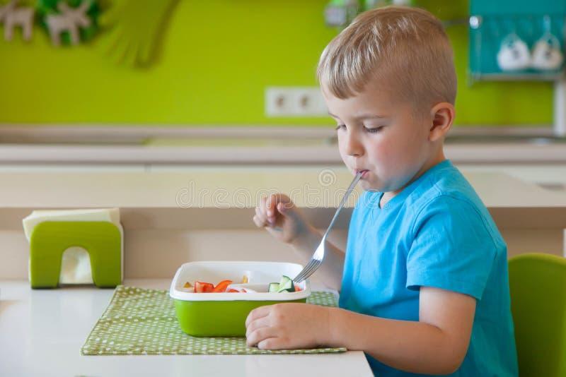 L'enfant que le garçon se corrompt à la table photo stock