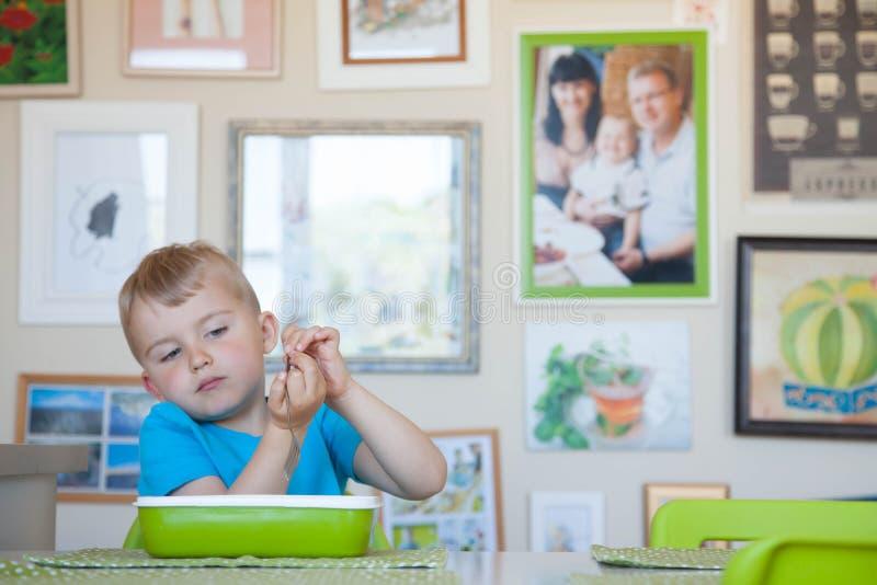 L'enfant que le garçon se corrompt à la table image stock