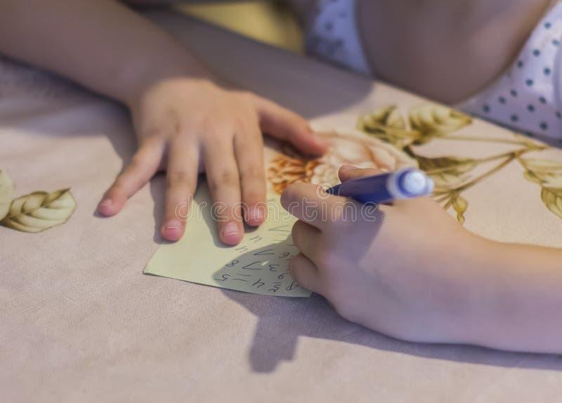L'enfant résout des exemples à la table images stock
