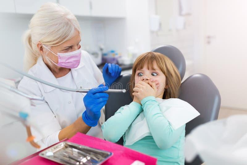 L'enfant refuse de montrer ses dents à la clinique dentaire photo stock