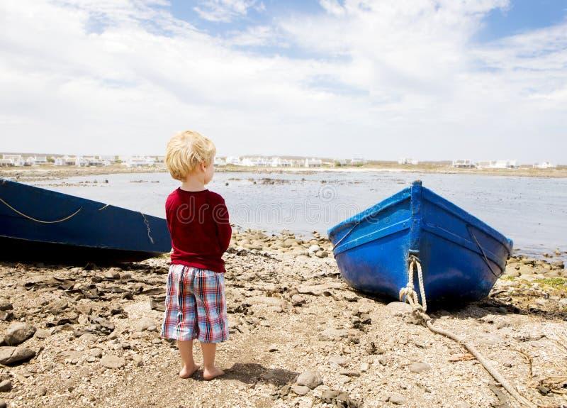 L'enfant regarde fixement au-dessus d'une baie avec des bateaux de pêche photo libre de droits