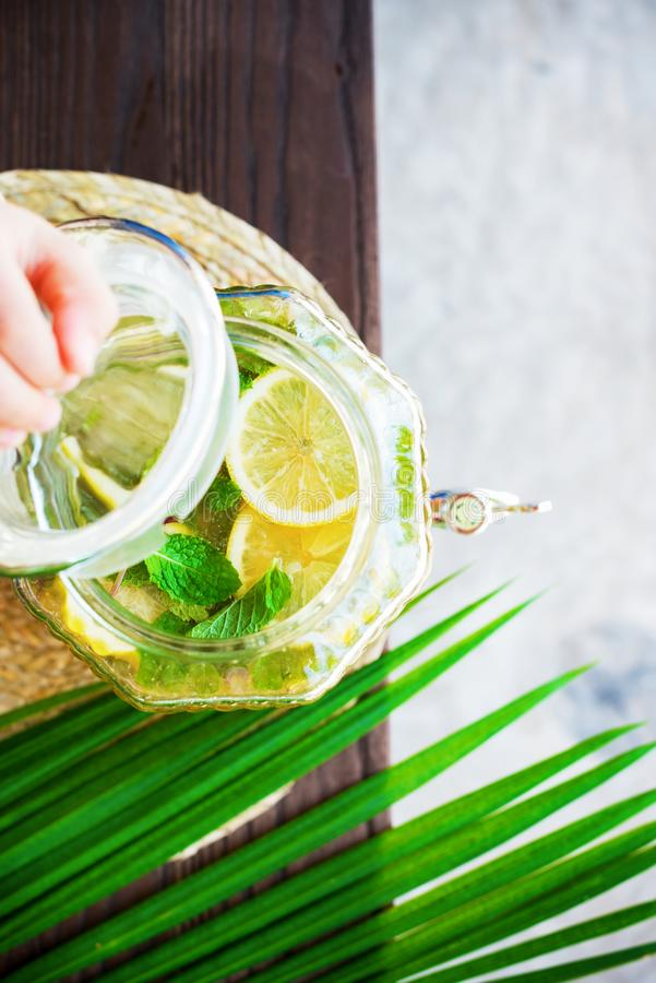 L'enfant remet à pot de couvercle d'ouverture la limonade faite maison image stock