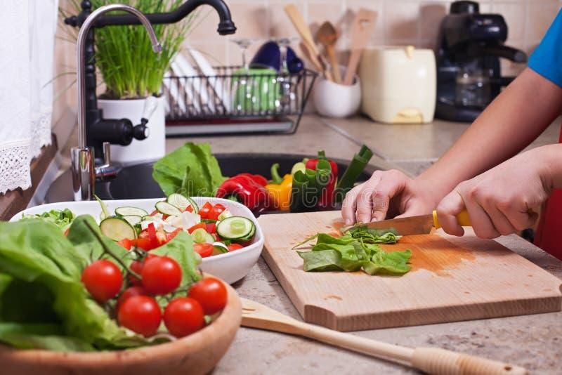 L'enfant remet couper des légumes sur la planche à découper - la laitue l photographie stock