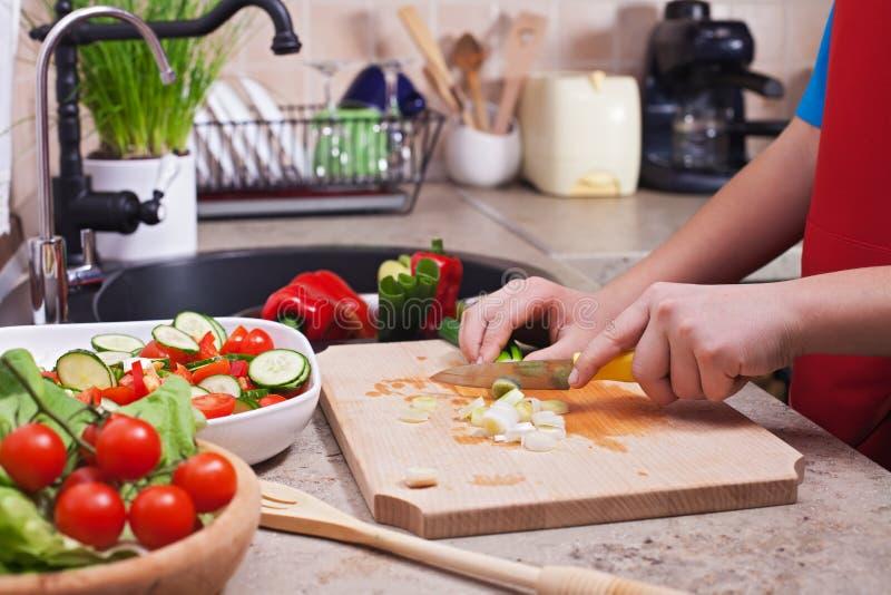 L'enfant remet couper des légumes sur la planche à découper - le ressort dessus images stock