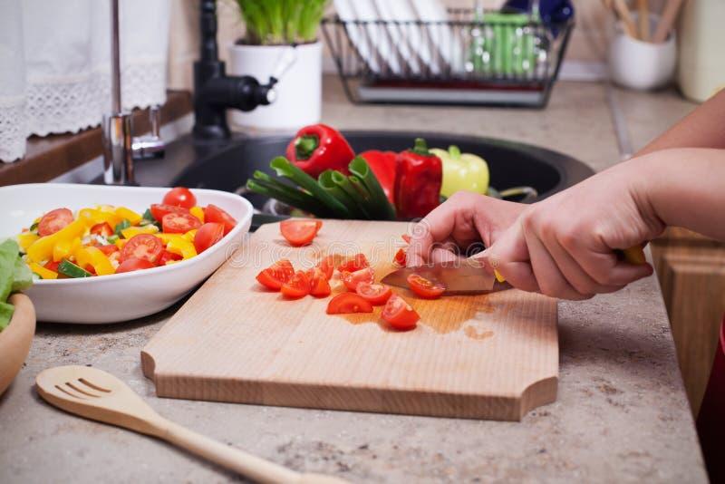 L'enfant remet couper en tranches des tomates-cerises pour une salade de légumes frais photo stock