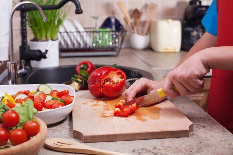 L'enfant remet couper un bellpepper rouge pour un sel de légumes frais image stock