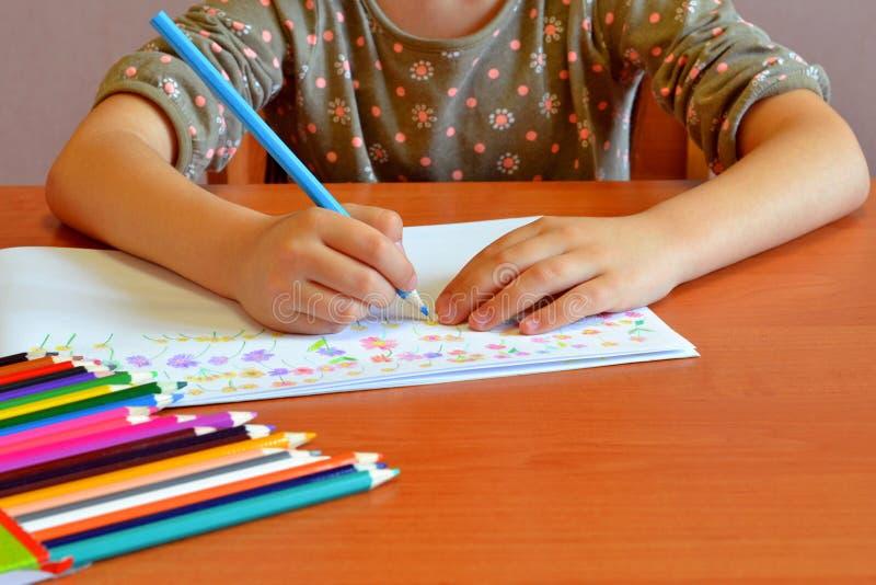 L'enfant repose et dessine des fleurs photo stock