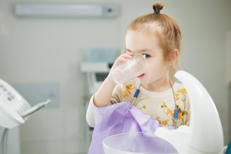 L'enfant rince la bouche et s'assied dans la chaise de dentiste images stock