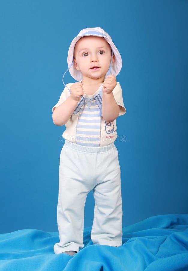 L'enfant sérieux se tient sur un fond bleu portant un costume de marin photo stock