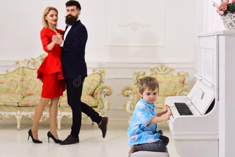 L'enfant s'asseyent ? c?t? du piano, musique de jeu, fond int?rieur blanc Concept d'?ducation de musicien Les parents riches appr photos libres de droits