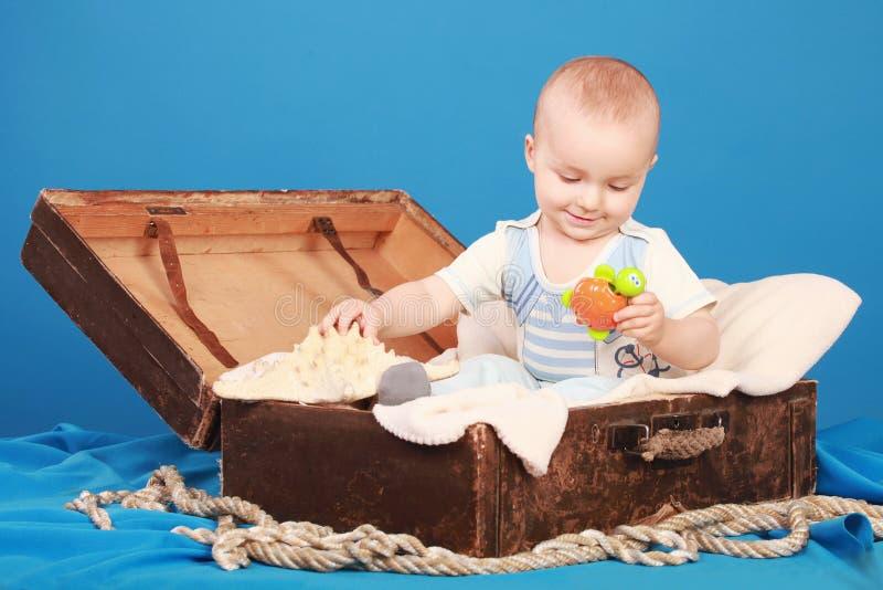 L'enfant s'assied dans un coffre dans un costume de marin et regarde une tortue de jouet photographie stock