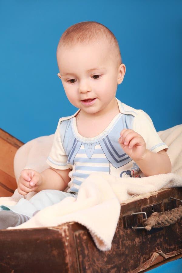 L'enfant s'assied dans un coffre dans un costume du ` s de marin et regarde son pied image stock
