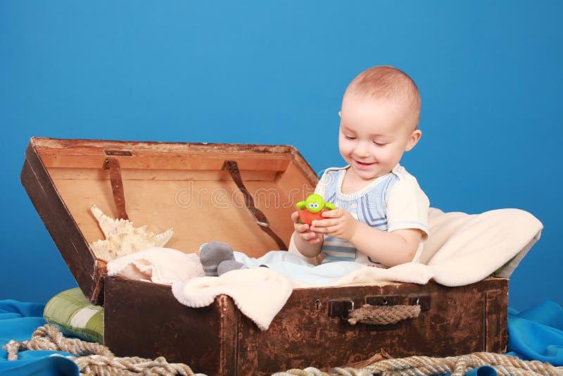 L'enfant s'assied dans un coffre sur un fond bleu dans un costume de marin photographie stock libre de droits