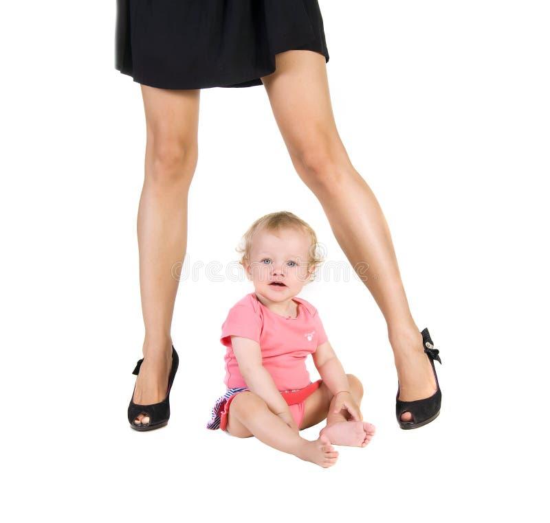 L'enfant s'assied entre les jambes femelles dans des chaussures photographie stock libre de droits