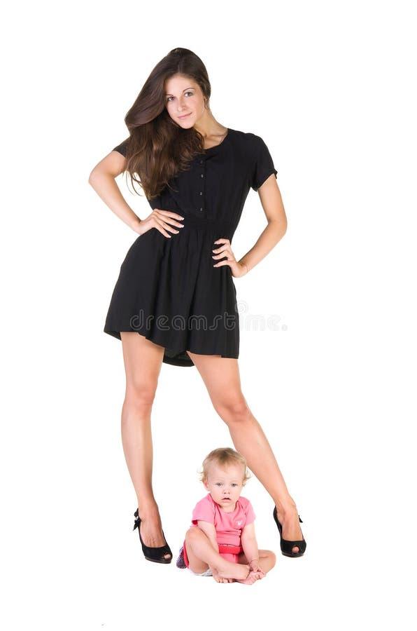 L'enfant s'assied entre les jambes femelles dans des chaussures photos stock