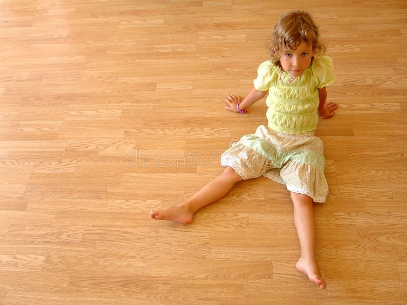 L'enfant s'assied sur l'étage en bois photo stock