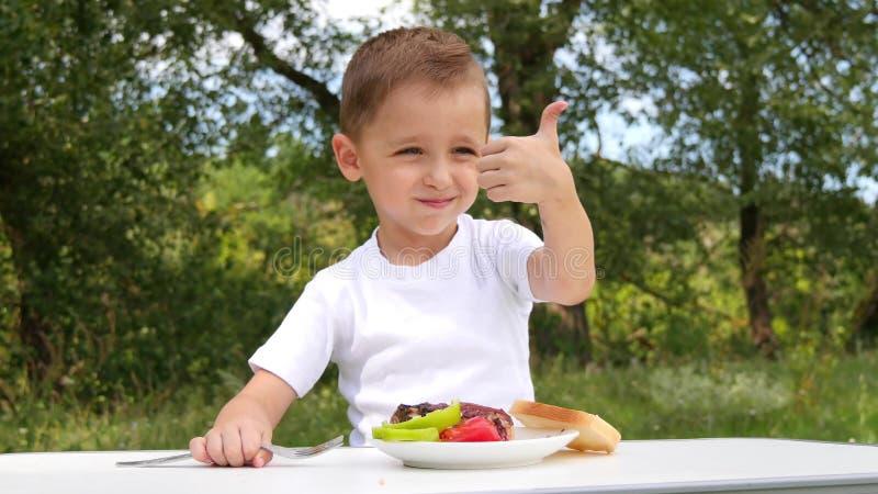 L'enfant s'assied sur le fond d'une forêt verte et mange le barbecue avec l'appétit Récréation extérieure et nourriture images libres de droits