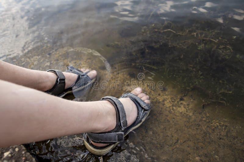 L'enfant s'assied sur le rivage du lac et a abaissé ses pieds chaussés en sandales dans l'eau, pour se refroidir un jour chaud d' photos libres de droits