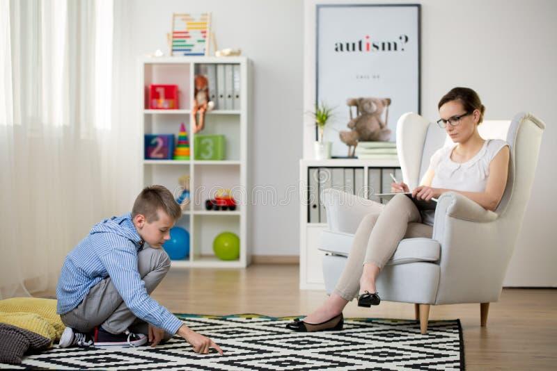 L'enfant s'assied sur le tapis images libres de droits