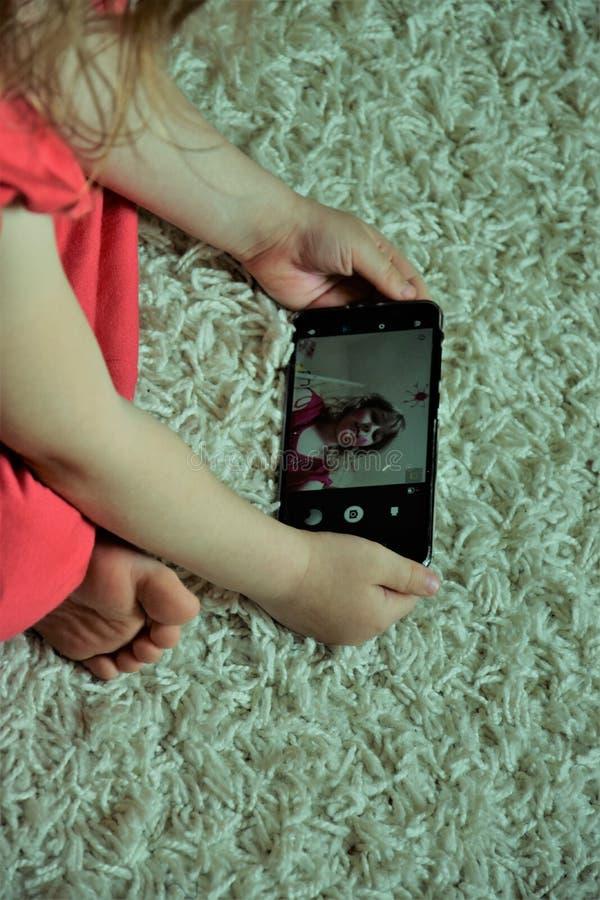 L'enfant s'enregistre sur le smarthone photos stock
