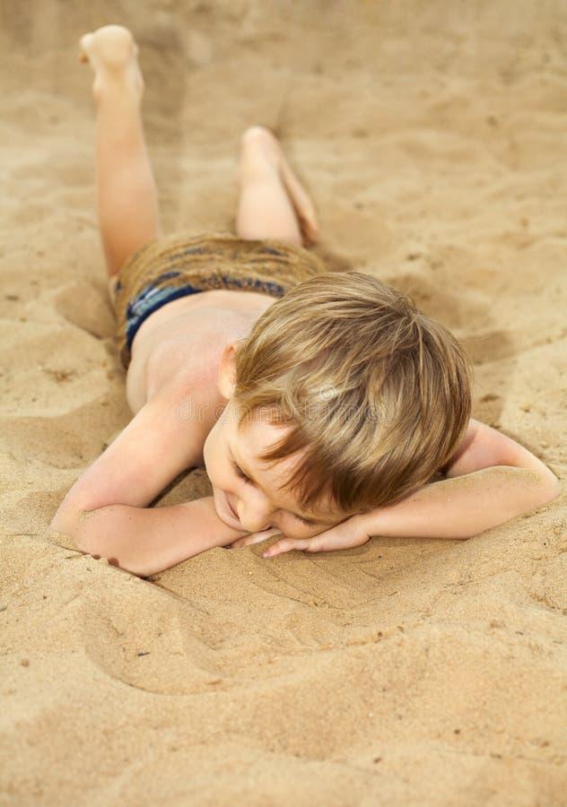 L'enfant s'expose au soleil sur une plage image libre de droits