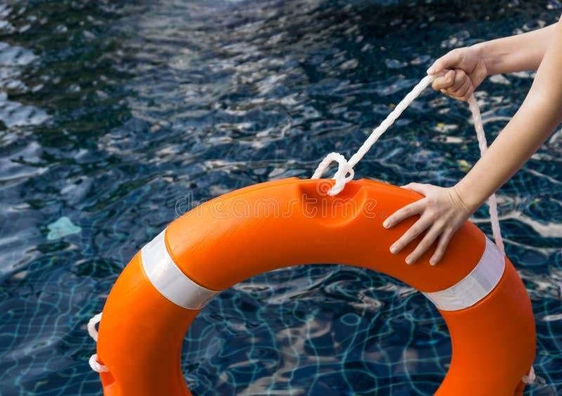 L'enfant `` s remet tenir la bouée de sauvetage contre l'eau foncée dangereuse dans la piscine Sécurité, concept de craintes de p images stock