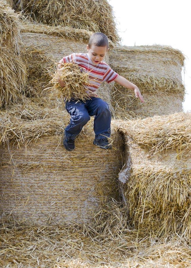 L'enfant sautant dans la meule de foin images stock