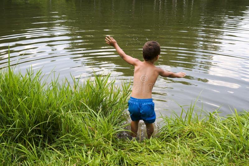 L'enfant sautant dans le lac ou l'étang photos stock