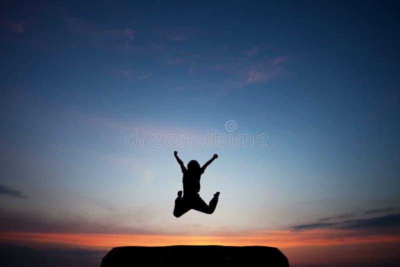 L'enfant saute en ciel de coucher du soleil photo libre de droits