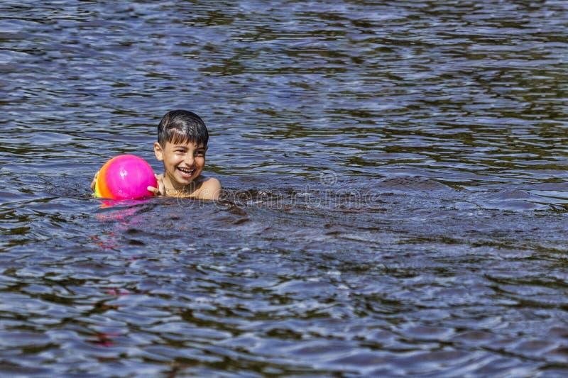 L'enfant se baigne dans le lac avec la boule que le petit garçon nage dans le lac pendant l'été image stock