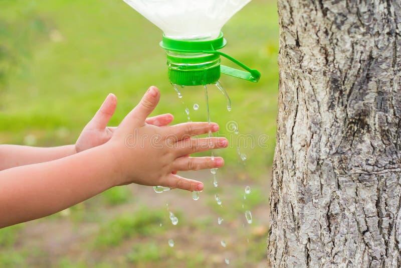 L'enfant se lave les mains sur la rue photo libre de droits