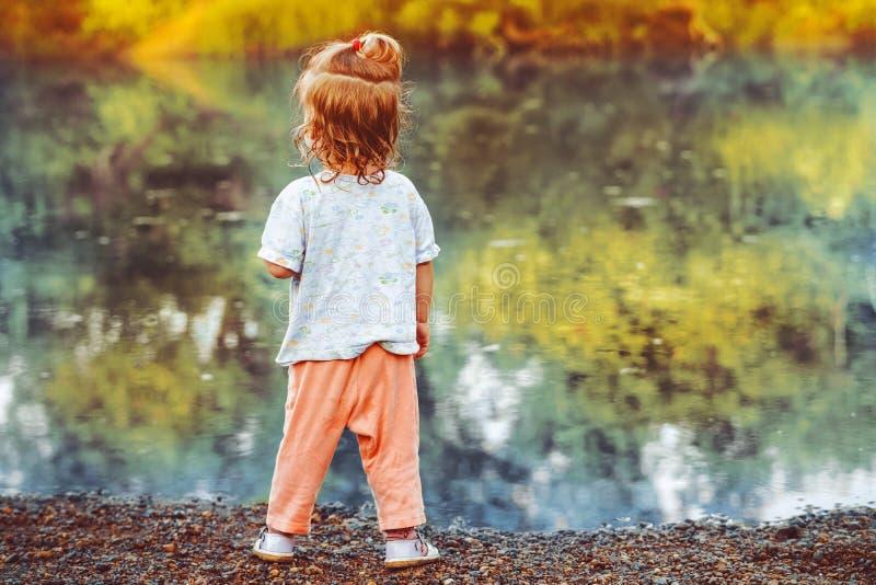 L'enfant se tient prêt la rivière photographie stock libre de droits